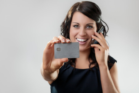 Beautiful woman holding a credit card on the phone maybe she's buying something Stock Photo - 26033534