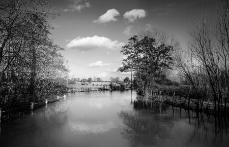 after large downpour of rain a river has burst its banks and flooded the near by fields in essex england photo