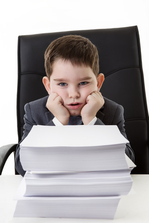 heap of role: young small boy pretending hes working in an office not looking very happy with all the paper work infront of him