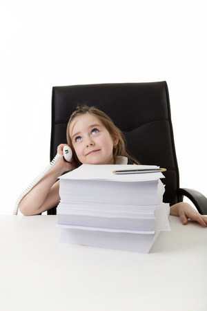 heap of role: young small girl pretending shes working in a office answering the phone with a large pile of paper work infront of her