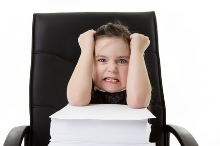 heap of role: young small girl pretending shes working in a office looking very mad and unhappy with the lager pile of paper work she has infront of her pulling out her hair