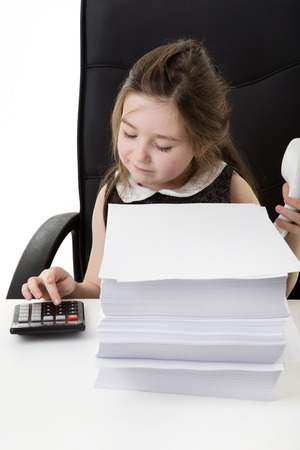 heap of role: young small girl pretending shes working in a office using a calculator Stock Photo