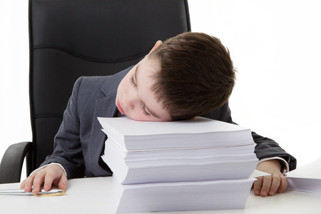 heap of role: young small boy pretending hes working in an office asleep at his desk on a large pile of paper work to do