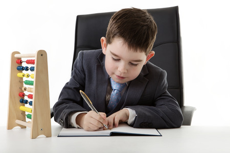 young small boy pretending hes working in an office with a abacus on his desk