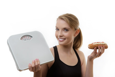 woman holding scale and a cream cake