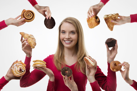 young woman surrounded by many cakes photo