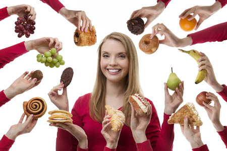 young woman surrounded my many cakes and fruits not sure what to eat