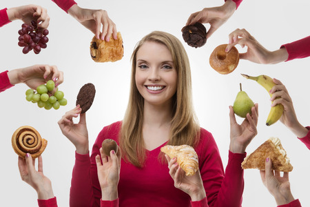 what to eat: young woman surrounded my many cakes and fruits not sure what to eat