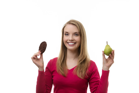 woman holding up a chocolate chip cookie and a pear not sure what to eat photo