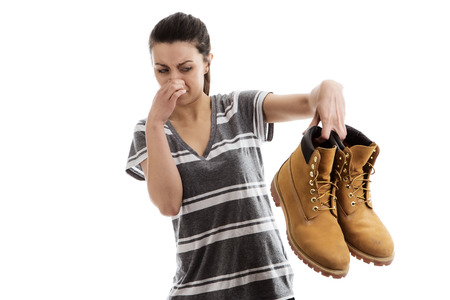 woman holding a pair of men smelly work boots in the air not looking to happy