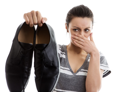 woman holding a pair of men smelly work shoes in the air not looking to happy