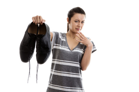 work shoes: woman holding a pair of men smelly work shoes in the air not looking to happy