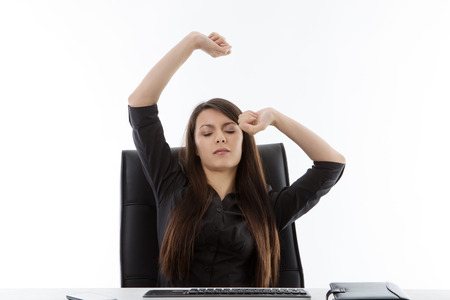 office worker sitting at her desk sleepy and stretching her arm out in the air photo