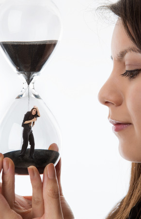 woman holding up a hour glass sand timer watching herself trapped in there photo
