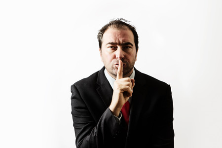 businessman with his finger up to his lips telling you to be quite