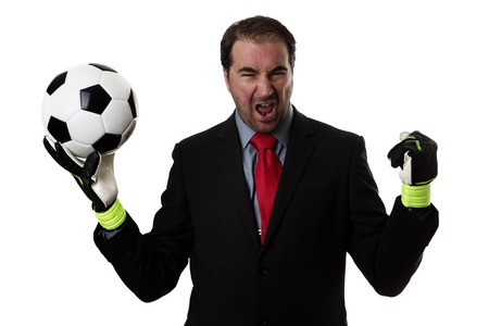 Business man holding a traditional black and white football wearing goalie gloves