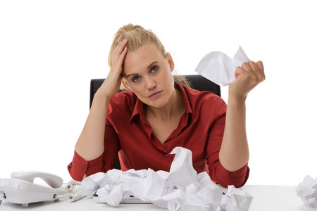 screwed: office worker with screwed up paper ball on her desk not looking to happy