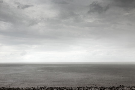 mersea: shot taken on east mersea island looking out across the sea with a moody sky as it raining hard