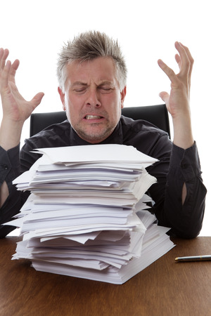 over worked: over worked businessman with a stack of paper work  infront of him sitting on his desk Stock Photo