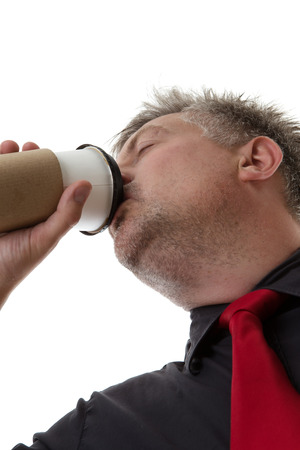 businessman drinking coffee from a paper cup taken from a low angle photo