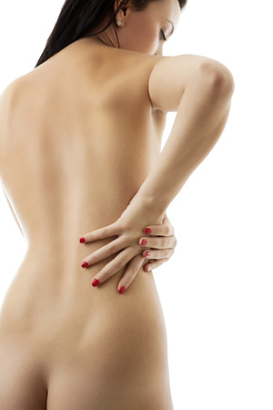 woman with her hand on her back showing signs of back pain