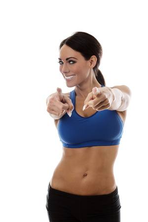 standing happy woman in sports bra and gym shorts pointing at you
