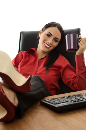 businesswoman with her feet up on an office desk drinking tea or coffee from at cup photo