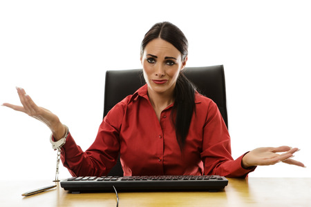 handcuffed: woman handcuffed to her desk at work Stock Photo
