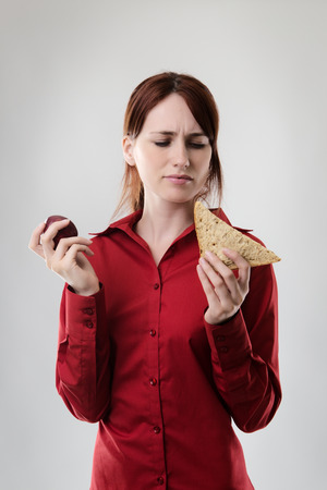 what to eat: business woman holding a sandwich and an apple not sure what to eat Stock Photo