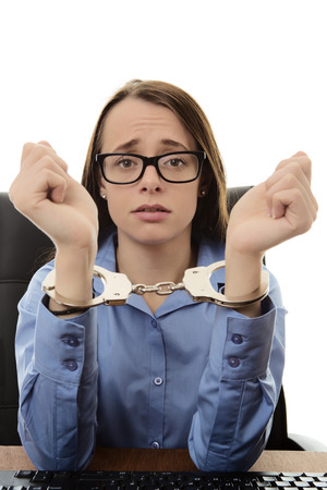 handcuffs woman: woman sitting at her desk at work with her hands  handcuffed together Stock Photo