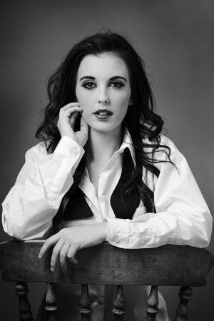 dishevel: bellezza ritratto di giovane donna girato in studio seduta su una vecchia sedia di legno