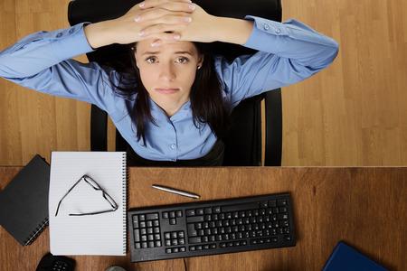vrouw bij haar bureau voelen de stress van het werk, genomen vanuit een vogelperspectief