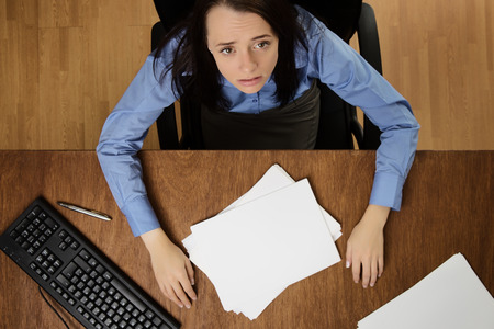 work load: woman working at her desk not happy about her work load, taken from a birds eye view Stock Photo