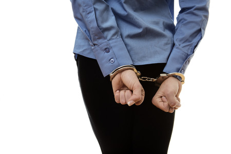 arrest women: business woman with her hands chained up in police handcuff