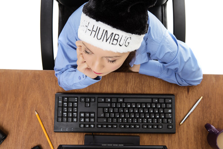 bah: woman at hers desk at work wearing a bah humbug christmas hat shot from a birds eye view looking down