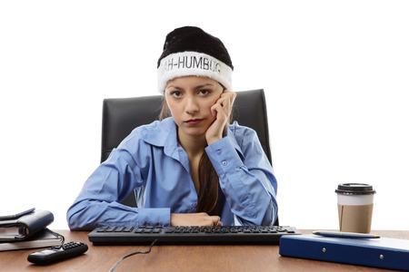 bah: woman at hers desk at work wearing a bah humbug christmas hat Stock Photo