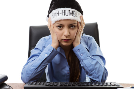 woman at hers desk at work wearing a bah humbug christmas hat Stock Photo