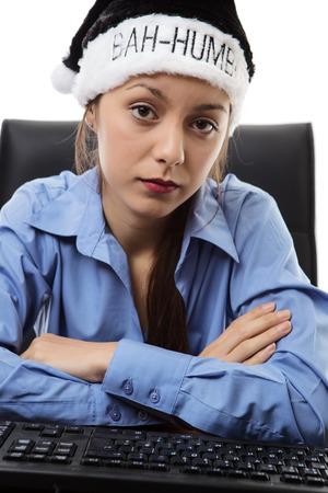 humbug: woman at hers desk at work wearing a bah humbug christmas hat Stock Photo