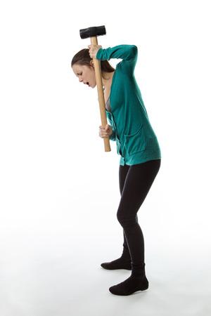 smashing: woman holding a large sledgehammer smashing the ground