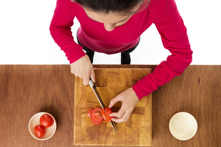 woman chopping up tomatoes on a wooden chopping board taken from a birds eye view from above