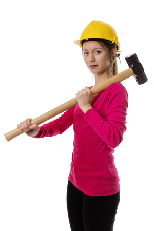 woman holding a sledgehammer and wearing a hard hat about to smash something Stock Photo
