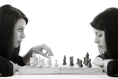 jugando ajedrez: mujer joven que juega al ajedrez contra sí misma un disparo en el estudio Foto de archivo