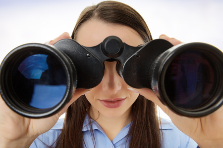 attractive business woman looking through binoculars Stock Photo