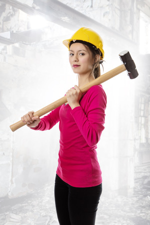 sledgehammer: woman holding a sledgehammer and wearing a hard hat about to smash something Stock Photo