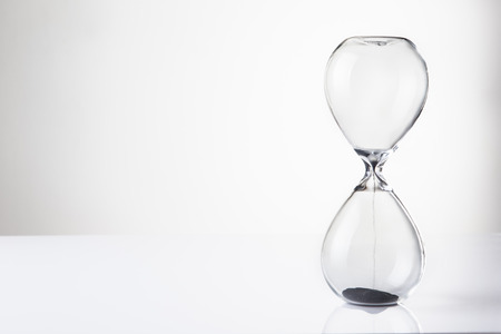 large hour glass sand timer with very little sand in there, time runs our quickly Stock Photo