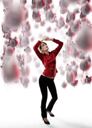 arms above head: standing woman with arms up above her head protecting  her self from falling clocks Stock Photo