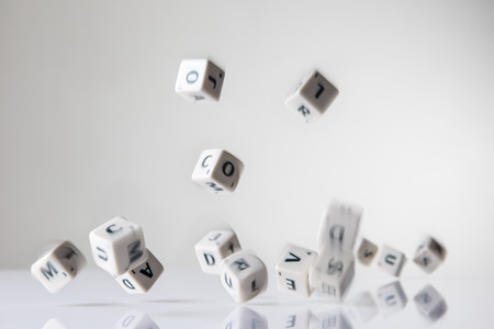 falling cubes: still life image of letter dice falling from the sky Stock Photo