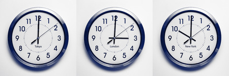 zones: clock on the wall of time zones for trading around the world set at 3PM london GMT time. image is black and white with a blue tint Stock Photo