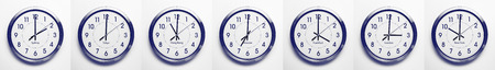time zones: clock on the wall of time zones for trading around the world set at 3PM london GMT time. image is black and white with a blue tint Stock Photo