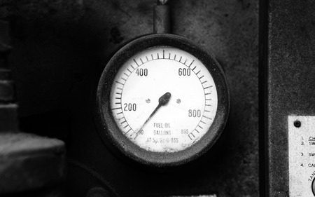 fuel gauge: Old fuel gauge on the wall showing empty Stock Photo